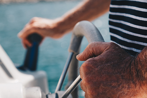 Close-up of Hand of Senior Captain on steering wheel of motor boat.