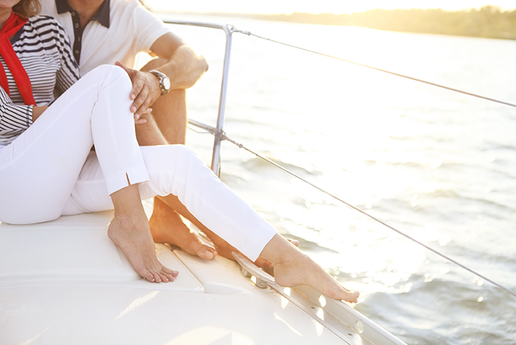 ?ouple stting on sailboat deck in the sea